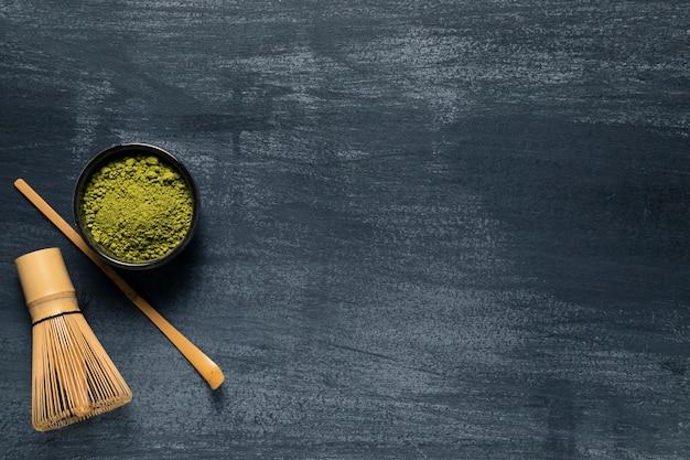 伝統的な泡立て器の横にある分離された緑茶のトップビュー 無料写真