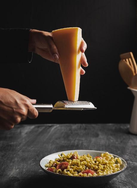 クローズアップの人がチーズを細断処理 無料写真