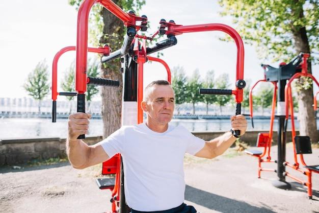 年配の男性が腕の筋肉を行使 無料写真