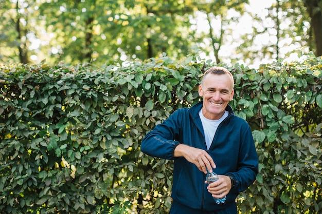 老人は水のボトルを手で押しながら笑顔 無料写真