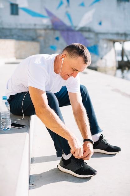 彼の右の靴ひもを結ぶ男 無料写真