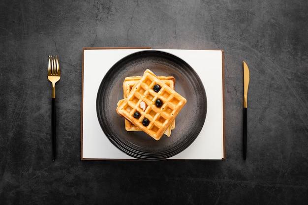 Вид сверху набор из двух вафель с золотыми столовыми приборами Бесплатные Фотографии