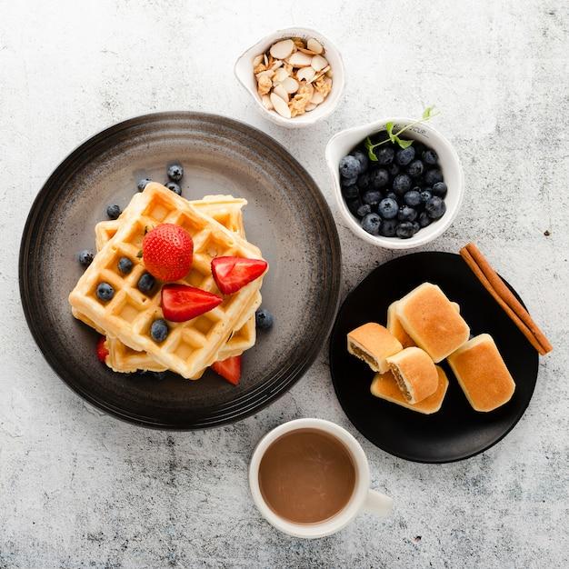 コーヒーとフルーツのパンケーキのトップビューセット 無料写真