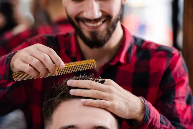 Парикмахер измеряет волосы перед стрижкой Бесплатные Фотографии