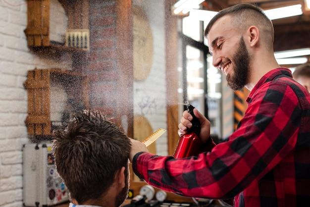 Счастливый парикмахер, распыляющий волосы клиента Бесплатные Фотографии