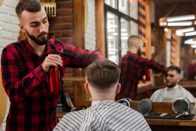 Парикмахер окропляет волосы молодого человека Бесплатные Фотографии