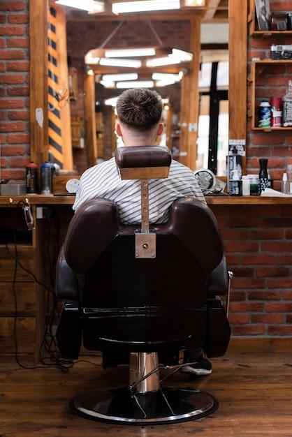 鏡で見ている椅子に座っている男 無料写真