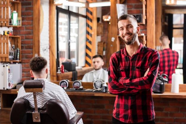 Улыбающийся молодой парикмахер с рубашкой Бесплатные Фотографии