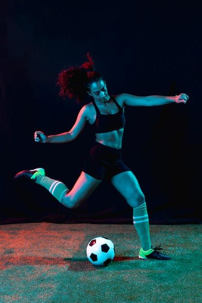 Спортивная молодая девушка пинает мяч Бесплатные Фотографии