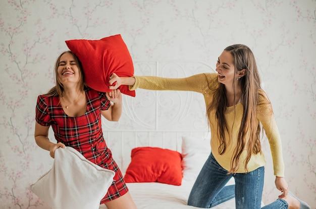 枕の戦いでミディアムショットスマイリー女の子 無料写真