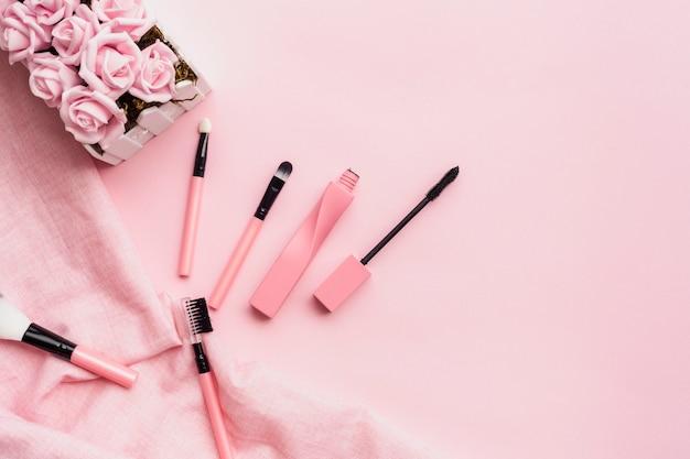 ピンクの背景のメイクアップアイテムとトップビューの配置 無料写真