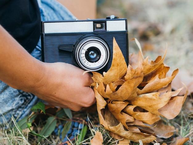 Крупный план фотоаппарата, проведенного женщиной Бесплатные Фотографии