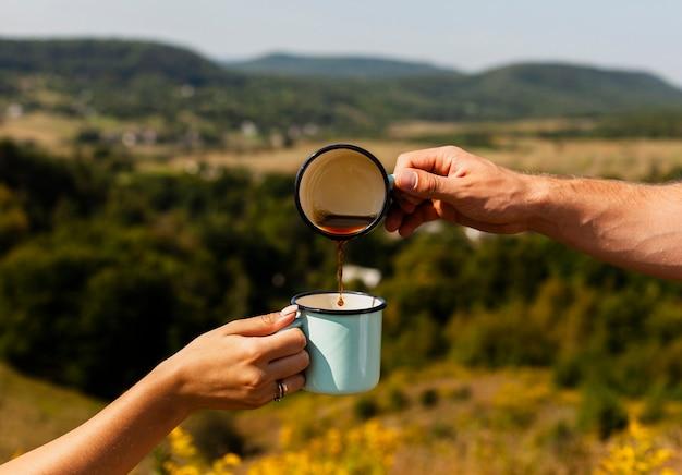 女性が保持している別のカップにコーヒーを注ぐ男 無料写真