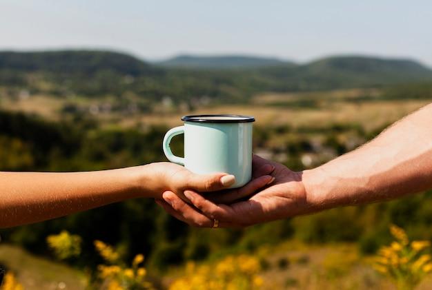 女性の手と一杯のコーヒーを保持している男 無料写真