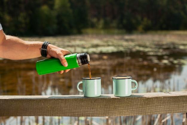 カップに飲み物を注ぐ手 無料写真