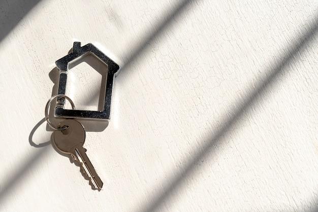 影と白い背景の上の家の鍵 無料写真