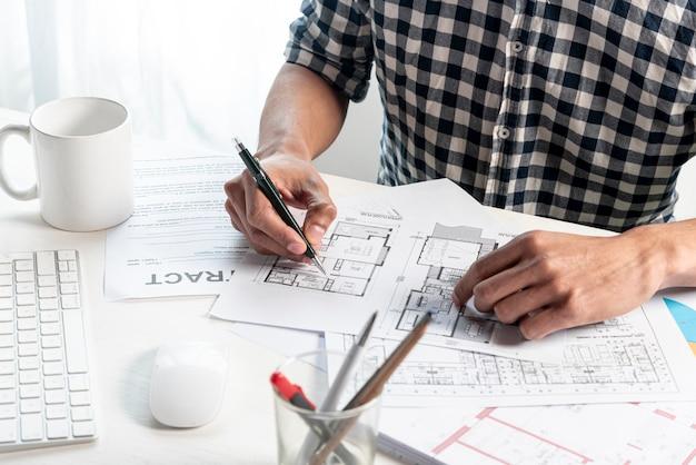 Высокий вид человека, создающего план дома Бесплатные Фотографии