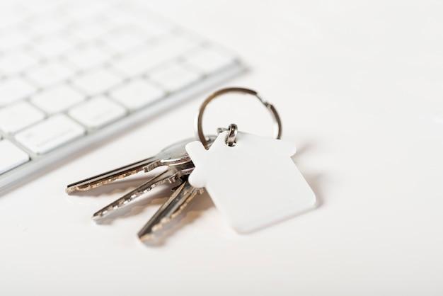 Клавиатура и ключи от дома на белом фоне Бесплатные Фотографии