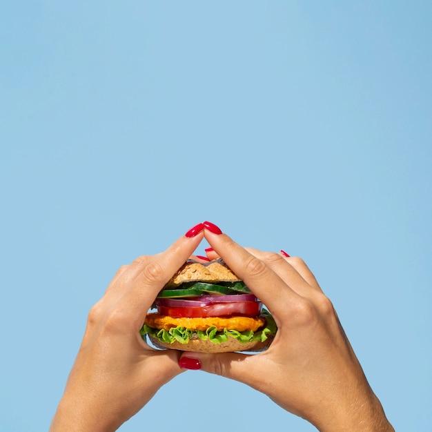 おいしい野菜のハンバーガーを保持しているクローズアップの人 無料写真