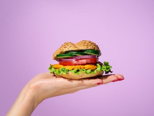 彼女の手のひらにおいしいハンバーガーを保持している女性 無料写真