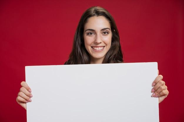 Вид спереди смайлик женщина, держащая пустой баннер Бесплатные Фотографии