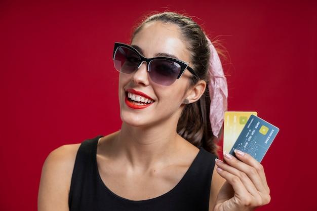 Фасонируйте женщину показывая ее кредитные карточки Бесплатные Фотографии