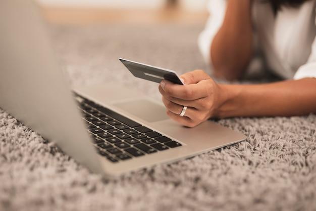ノートパソコンの横にクレジットカードを持っているクローズアップ手 無料写真