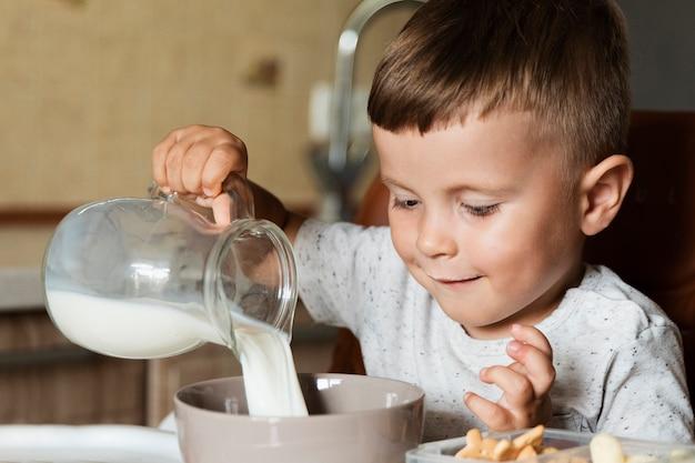 Счастливый малыш наливает молоко в миску Бесплатные Фотографии