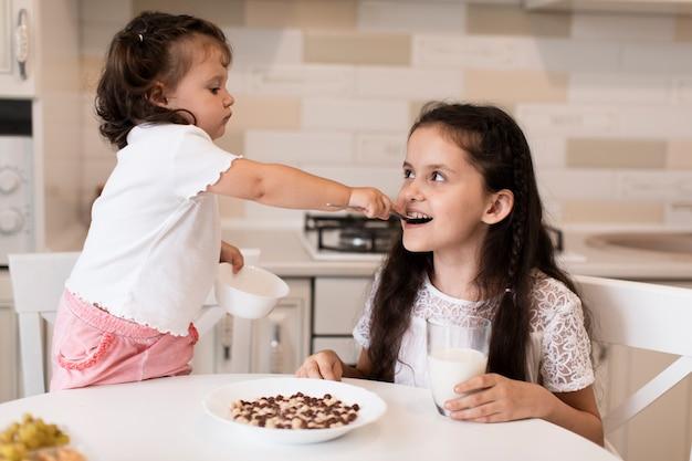 Очаровательная молодая девушка кормит свою сестру Бесплатные Фотографии