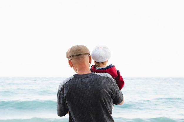 フロントビューのおじいちゃんと海辺での孫 無料写真
