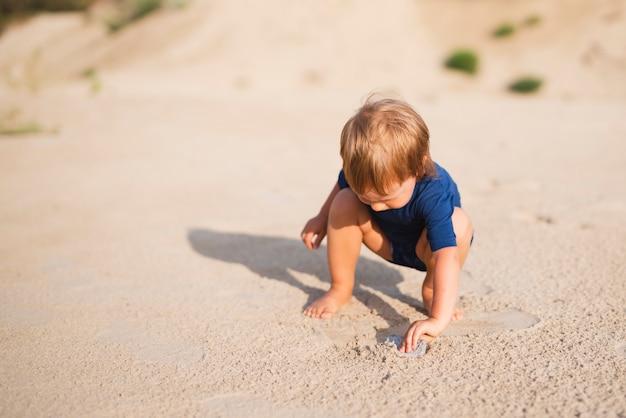 砂と遊ぶビーチで高角度の小さな男の子 無料写真