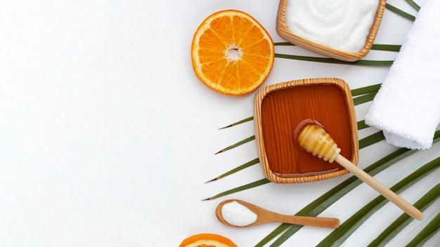 コピースペースを持つ蜂蜜とオレンジスライスのトップビュー 無料写真