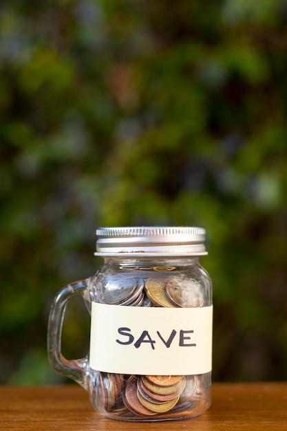 コインで瓶し、背景をぼかした写真のラベルを保存 無料写真
