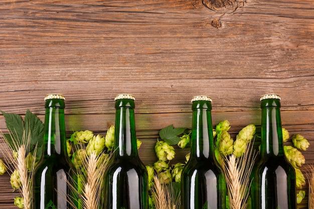 木製の背景に緑色のビール瓶 無料写真