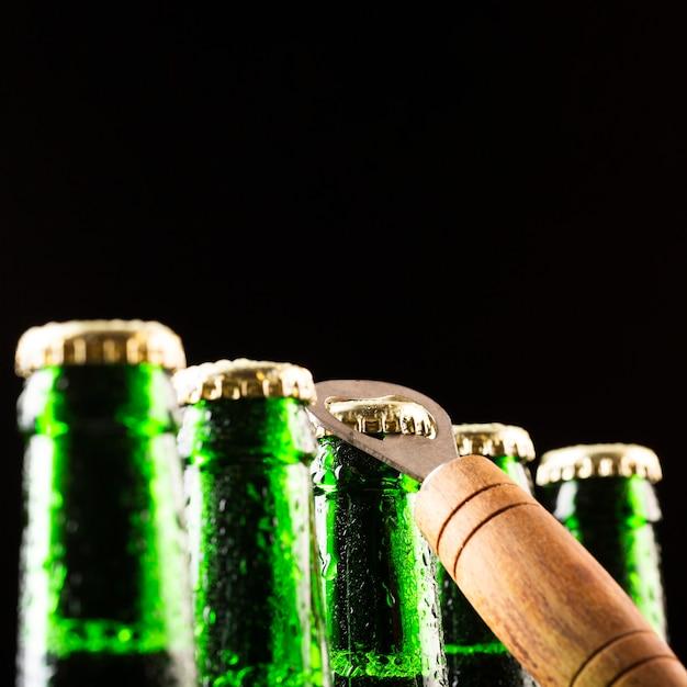 Пивные бутылки стоят на ряду и открывашка Бесплатные Фотографии