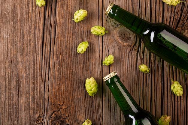 ビール瓶と木製の背景上のホップ 無料写真