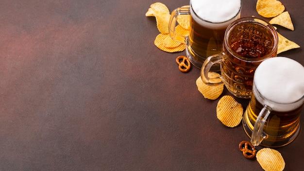 泡とスナック付きのビールジョッキ 無料写真