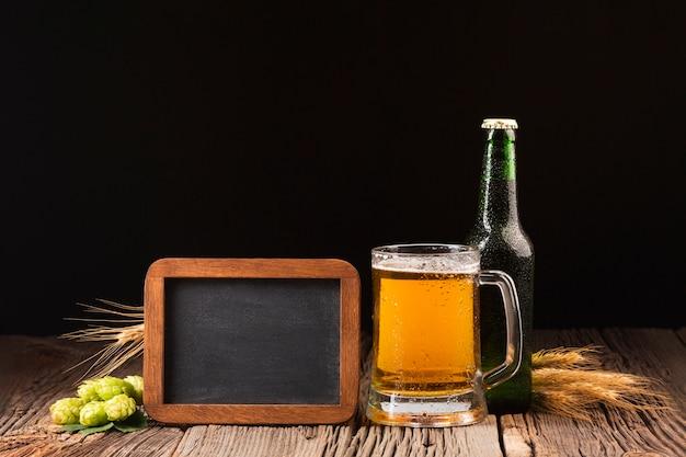 マグカップと木製の背景にビールの瓶 無料写真