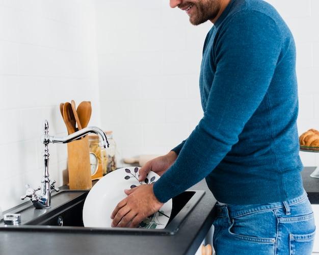 お皿を洗うクローズアップ若い男 無料写真