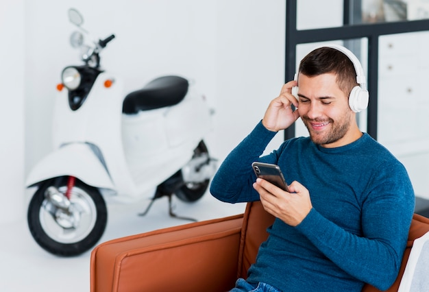 音楽の携帯電話をチェックするヘッドフォンを持つ男 無料写真