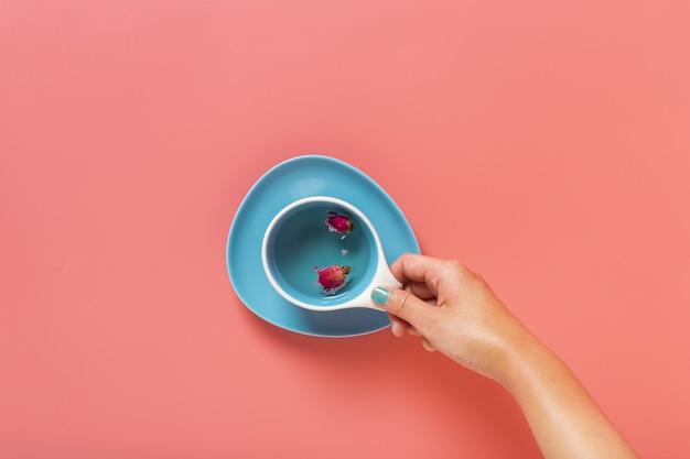 無地の背景を持つカップを持っている手のフラットレイアウト 無料写真