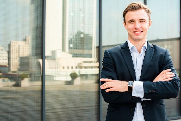 カメラを見て組んだ腕に笑みを浮かべて実業家 無料写真