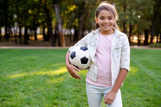 Улыбающаяся девушка смотрит в камеру и держит мяч Бесплатные Фотографии