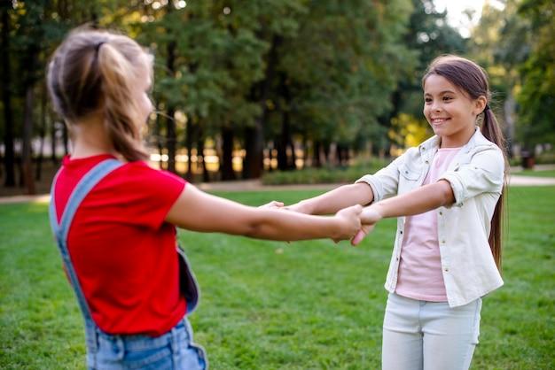Девушки держатся за руки на открытом воздухе Бесплатные Фотографии