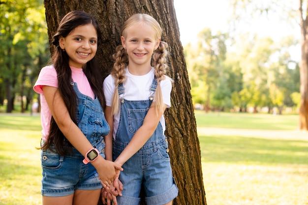 Улыбающиеся молодые подружки держатся за руки Бесплатные Фотографии