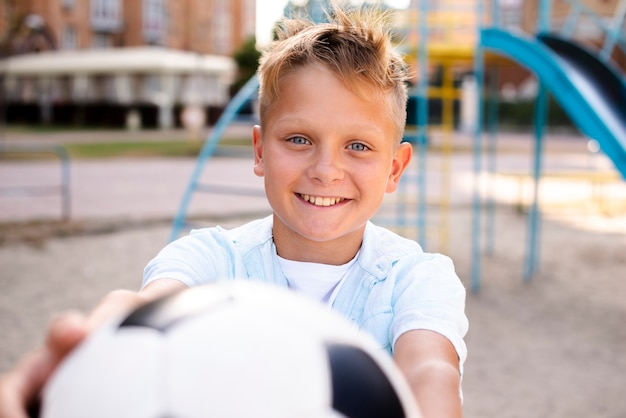 Мальчик протягивает футбольный мяч к камере Бесплатные Фотографии