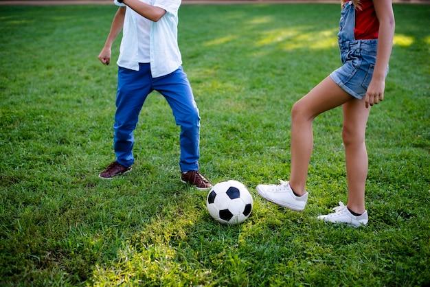 Двое детей играют в футбол на траве Бесплатные Фотографии