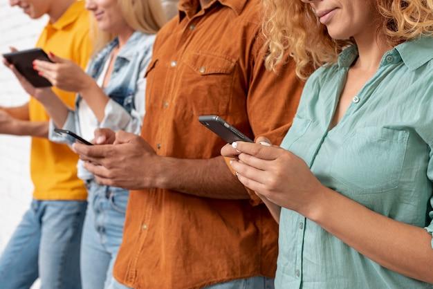 携帯電話を持つ友人のクローズアップグループ 無料写真