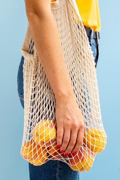 リンゴと白いメッシュバッグを保持している女性 無料写真