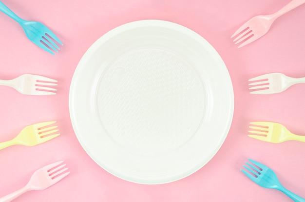 ピンクの背景にカラフルなプラスチック皿 無料写真